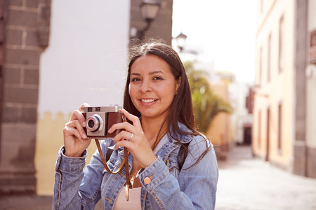 loose hair: Pretty young brunette taking pictures and looking at the camera wearing her long hair loose and casual clothing with a narrow street in her background