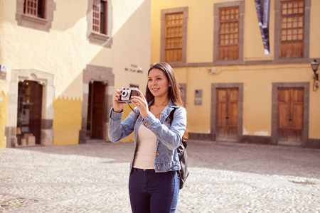 touristy: Pretty young girl taking touristy pictures while smiling a toothy smile and her hair loose wearing casual clothing with old buildings behind her