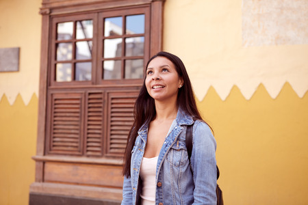 loose hair: Pretty young girl standing and looking up at the sky while smiling, her hair loose wearing casual clothing with an old building behind her