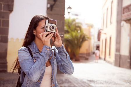 loose hair: Cute young lady focusing to take a picture with her camera wearing her hair loose and casual clothing with a narrow street in her background