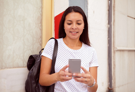 loose hair: Pretty young girl smiling at her cell phone while standing in front of a pillar, wearing her hair loose and a spotted t-shirt