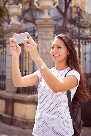 Cute young girl taking pictures with her cell phone while standing in front of old gates, wearing her hair loose and a spotted t-shirt