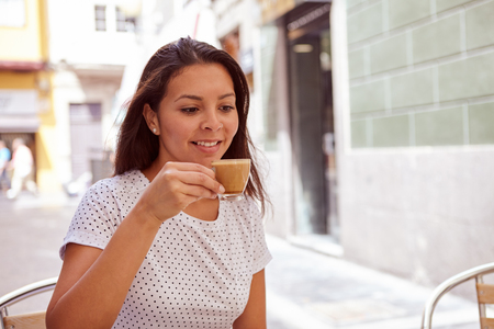 street cafe: Happily smiling young girl drinking coffee at a street cafe, relaxing while wearing her hair loose and casual clothing