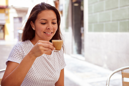 loose hair: Smiling young girl drinking coffee at a street cafe, relaxing while wearing her hair loose and casual clothing