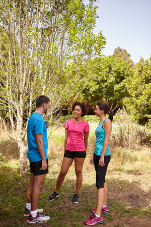 joggers: Three young joggers taking a break in daylight surrounded by trees and bushes in the late morning wearing t-shirts and black pants