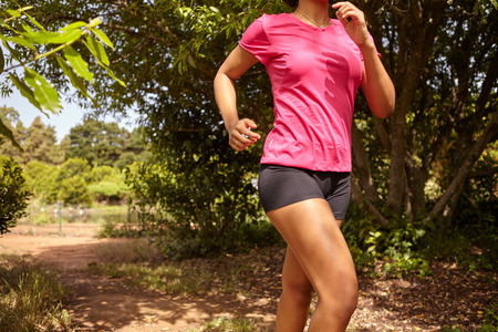 looking ahead: Female body showing from neck to knees running while wearing a pink t-shirt and black pants in a natural area surrounded by trees