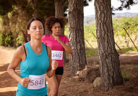 looking ahead: Two girls running a cross country race with trees behind them while wearing casual running clothes in the late morning