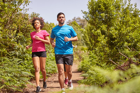 joggers: Three young joggers out for a run on a gravel path surrounded by bushes, wearing casual running clothes Stock Photo