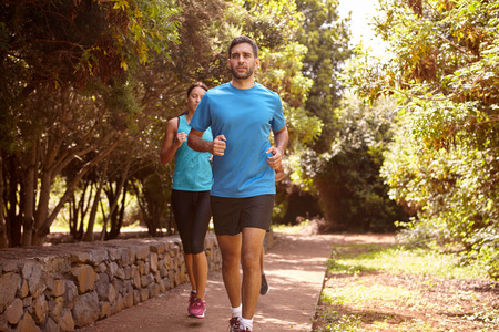 looking ahead: A guy and two girls running on a paved running trail with trees and a stone wall behind them wearing t-shirts and black pants Stock Photo