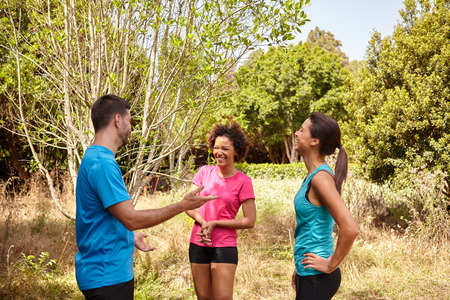joggers: Group of three young joggers taking a break in daylight surrounded by trees and bushes in the late morning wearing t-shirts and black pants