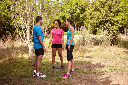 joggers: Three young joggers taking a break in the shade of the trees and bushes in the late morning wearing t-shirts and black pants