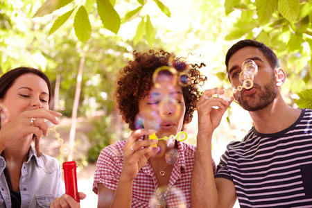 blowing bubbles: Three funloving friends blowing bubbles and smiling in the dappled afternoon sunshine with some trees around them wearing casual clothing