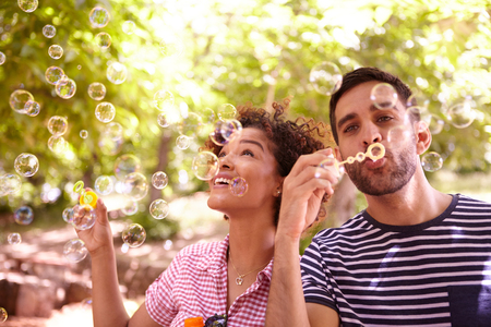 blowing bubbles: Two young friends joyfully blowing bubbles and smiling in the dappled afternoon sunshine with some trees around them wearing casual clothing Stock Photo
