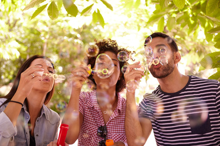 dappled: Three friends joyfully blowing bubbles and smiling in the dappled afternoon sunshine with some trees around them wearing casual clothing