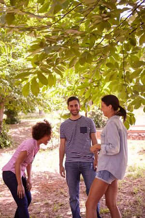 dappled: Three friends joking and laughing together in the dappled afternoon sunshine with some trees around them wearing casual clothing Stock Photo