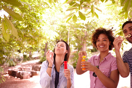 blowing bubbles: Three young friends laughing and blowing bubbles in the dappled afternoon sunshine with some trees around them wearing casual clothing