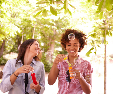 blowing bubbles: Two young girls laughing and blowing bubbles in the dappled afternoon sunshine with some trees around them wearing casual clothing Stock Photo