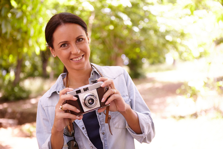 dappled: Smiling young woman holding an old style camera in the shade of some trees with dappled sunshine wearing casual clothing Stock Photo