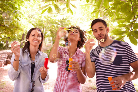 dappled: Three young people laughing and blowing bubbles in the dappled afternoon sunshine with some trees around them wearing casual clothing