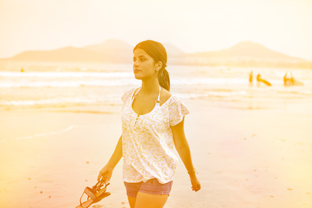 hair tied back: Healthy young brunette strolling on the beach with waves breaking, her hair tied back while wearing casual clothes