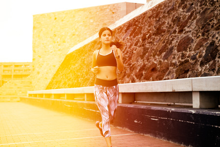 hair tied back: Young brunette running on a paved road next to a rock barrier, wearing casual clothes and running shoes with her hair tied back