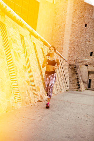 Concentrating brunette running with steps and buildings behind her, wearing casual clothes with her hair tied back