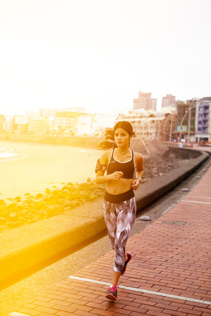 hair tied back: Young girl running on a paved path with a cityscape behind her, wearing casual clothes and running shoes and her hair tied back
