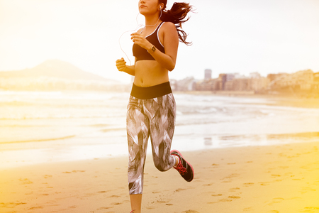 Young brunette with earphones running along the beach with her hair tied back while wearing casual clothes