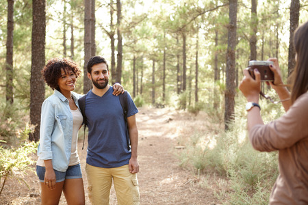 pine three: Three friends posing for pictures of each other in a pine forest in the late afternoon sunshine, looking ahead while wearing casual clothing