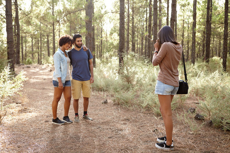 pine three: Three friends taking pictures of each other in a pine forest in the late afternoon sunshine, looking ahead while wearing casual clothing