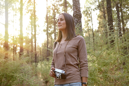 looking ahead: Young girl in a forest of pine trees holding her camera wonderingly looking ahead of herself while wearing a brown t-shirt and shorts