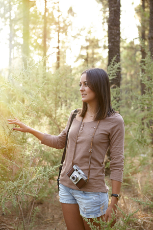 Wondering young girl smiling secretly looking ahead of herself in a forest of pine trees while wearing casual clothing