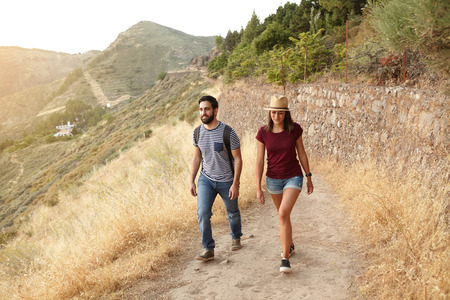back pack: Nice young couple strolling up a mountain in very bright sunlight wearing t-shirts and jeans and a straw hat and back pack at sunset