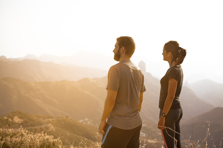 admiring: Two youngsters standing and admiring the view on a mountain in full sunlight with their hands to their sides