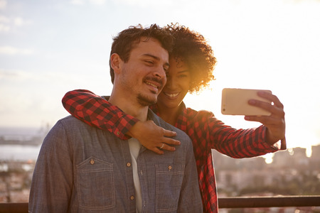 in loving memory: Loving young couple sharing a moment while taking a selfie to keep the memory alive with a city scape behind them