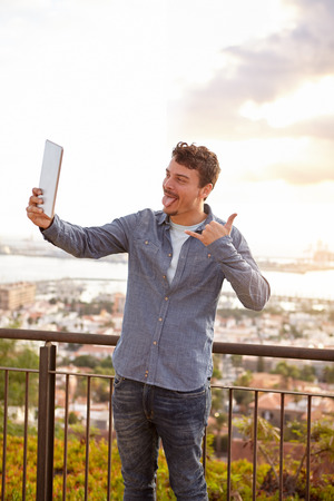 pulling faces: Young man pulling faces at his tablet and indicating a phone gesture while standing on a bridge Stock Photo