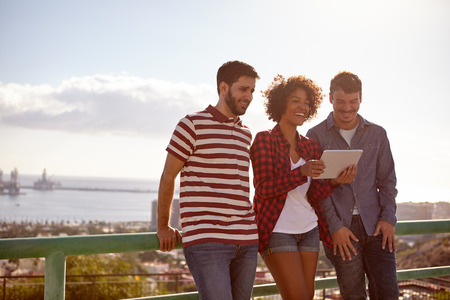 leaning against: Three laughing good looking friends leaning against a railing looking at a tablet, the girl between the young men is holding Stock Photo
