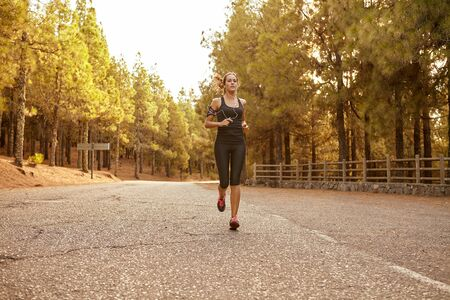 Young brunette woman running in a forest on a tarred road cutting through it with bright sunshine from behind her