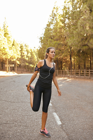 Pretty young brunette jogger stretching in a forest on a tarred road cutting through it with bright sunshine from behind her Stock Photo