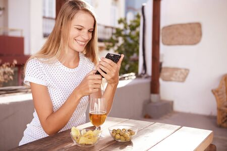 Smiling blond girl looking at her cellphone with a big toothy smile while sitting at a wooden table with a drink and bowls of snacks
