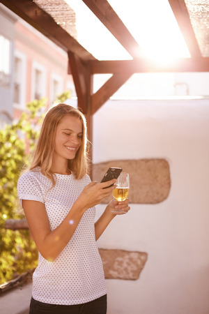 celphone: Lovely blond girl with a toothy smile looking at her celphone with a beer in the other hand and bright sunshine from behind Stock Photo