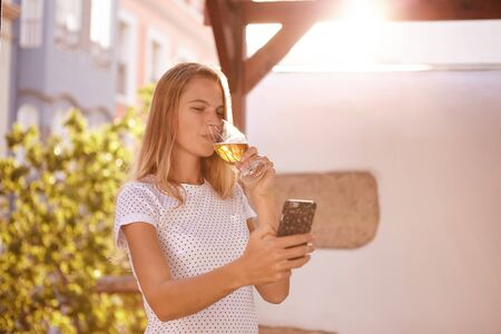 Pretty blond girl looking at her cellphone while sipping her beer in overexposed sunlight from behind her