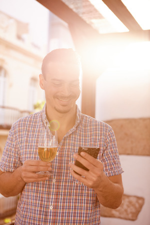 Man with a beer in one hand and a cellphone in the other standing with the very overexposed bright sun behind him