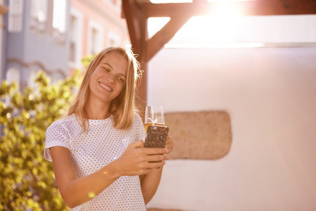 Lovely smiling blond girl looking at her cellphone while holding a beer and tilting her head sideways in bright sunshine Stock Photo