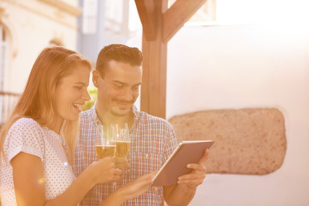 Good looking couple looking and pointing at something on the tablet while enjoying some beers whith the sun shining brightly behind them Stock Photo