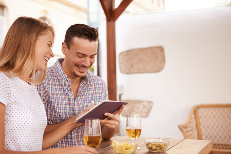 Happy young couple laughing while sharing a touchpad relaxing with beers and snacks on the table and bright sunshine behind them