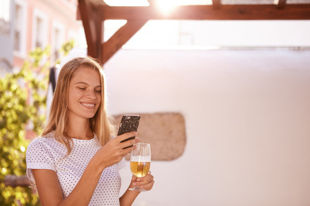 Pretty blond girl with a lovely smile looking at her cellphone while holding a beer in the other hand in overexposed sunlight