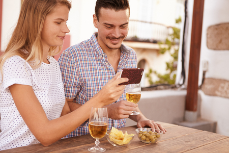 them: Sweet couple looking at cellphone she is holding with satisfied smiles while enjoying some beers and snacks and the sun shining behind them