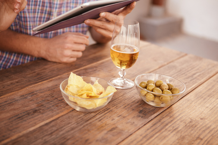Glass bowls with crispy chips and green olives arranged with a beer glass on a rustic wooden table with relaxed hands holding a touchpad Stock Photo