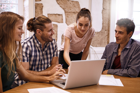 Professional young business team in an interactive and lively meeting in a conference room with a laptop pc on the desk Stock Photo